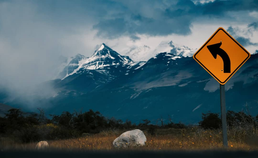 A sign with a mountain in the background